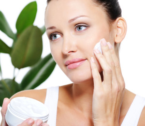 Woman applying moisturizer cream for her pretty face