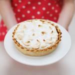 103332960-woman-holding-lemon-meringue-pie-gettyimages