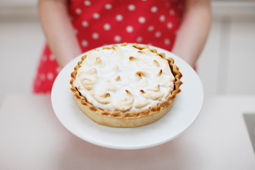 103332960-woman-holding-lemon-meringue-pie-gettyimages