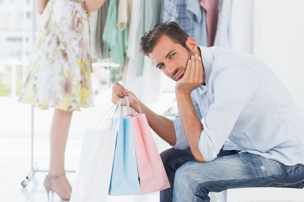 man with shopping bag bored while woman searches clothes rack