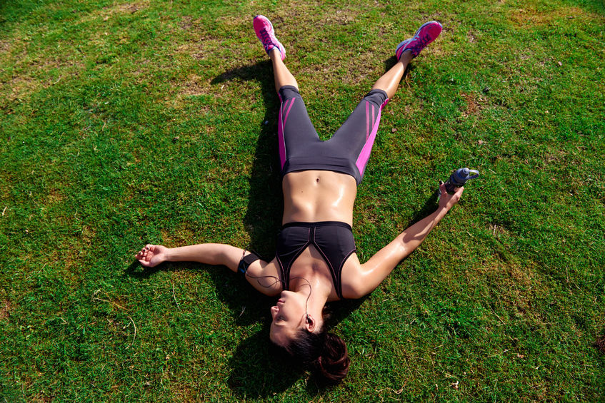 woman lying on grass, exhausted from running