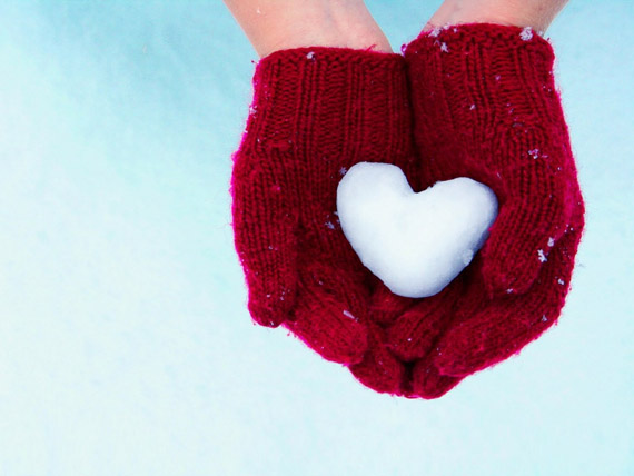 pair of cupped hands in red mittens holding heart-shaped snowball against a white and blue background