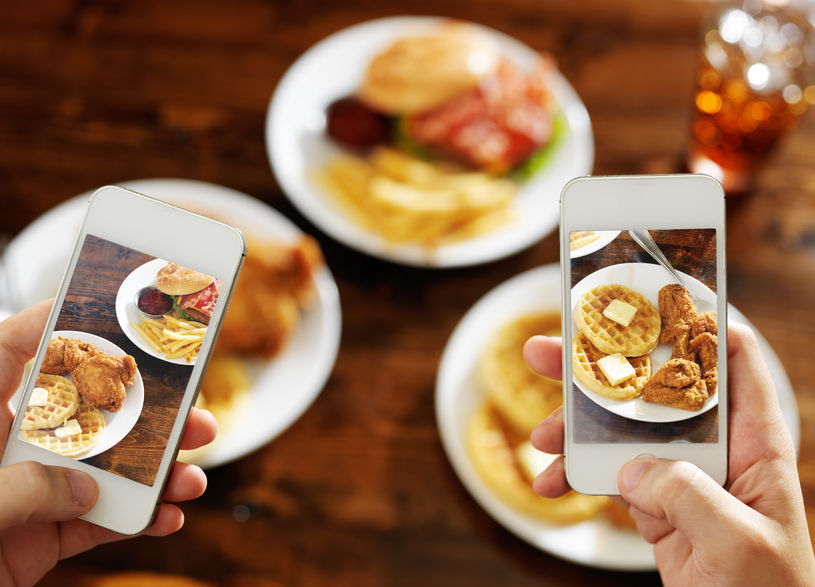 two smartphones taking images of breakfast plate