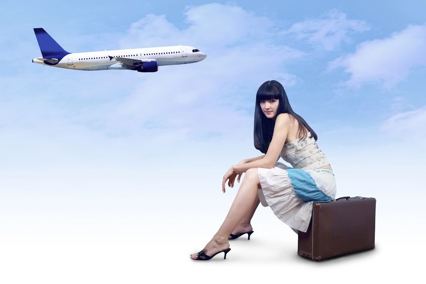 woman sitting on suitcase with plane in background