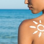 woman with sunblock in the shape of the sun on bare shoulder against ocean backdrop