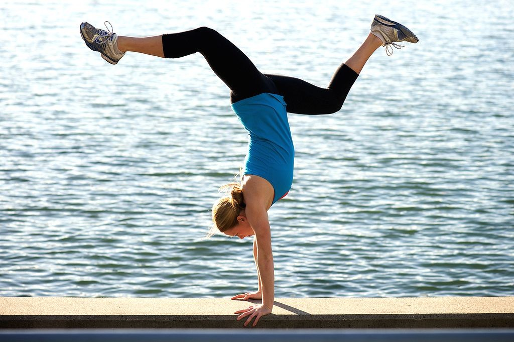 woman doing handstand in front of body of water