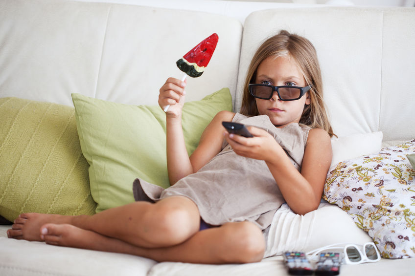 little girl watching TV sitting on sofa