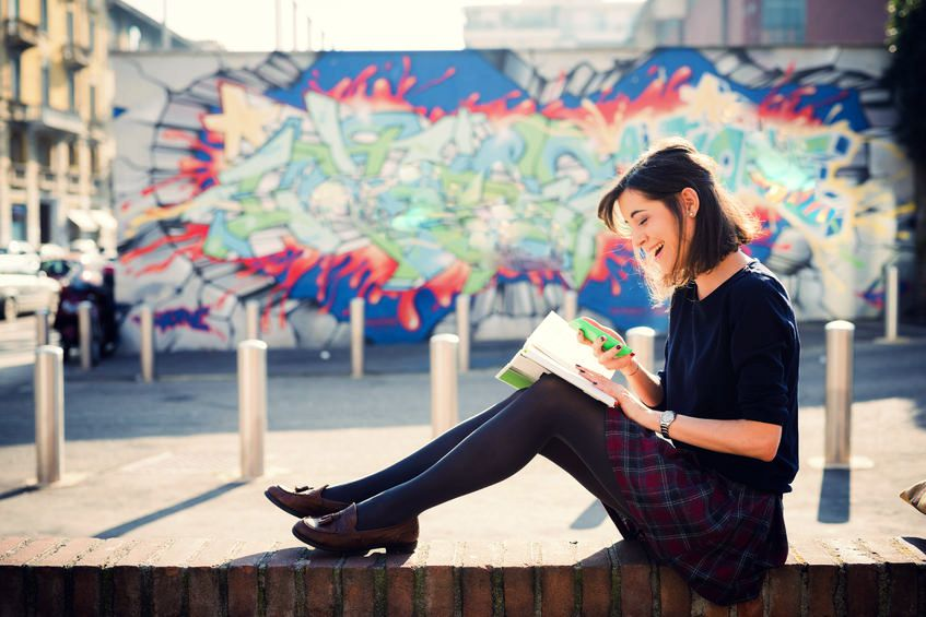 young smiling woman sitting down and reading book