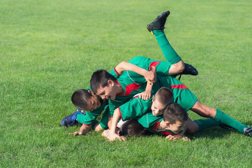 kids dogpiling on grass field