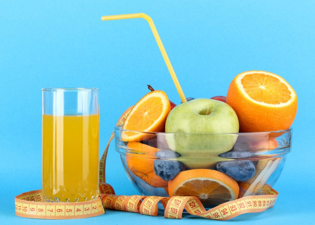Glass bowl with fruit for diet and juice on blue background