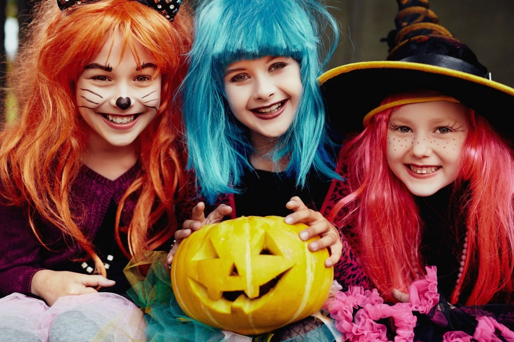Group of girls in Halloween costumes looking at camera with smiles