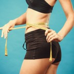 Fit fitness girl measuring her waistline with measure tape on blue