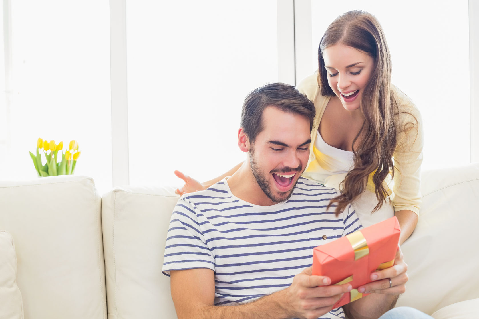 woman surprising her boyfriend with gift at home in the living room