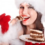 Girl in Santa hat eat cake on plate . Isolated