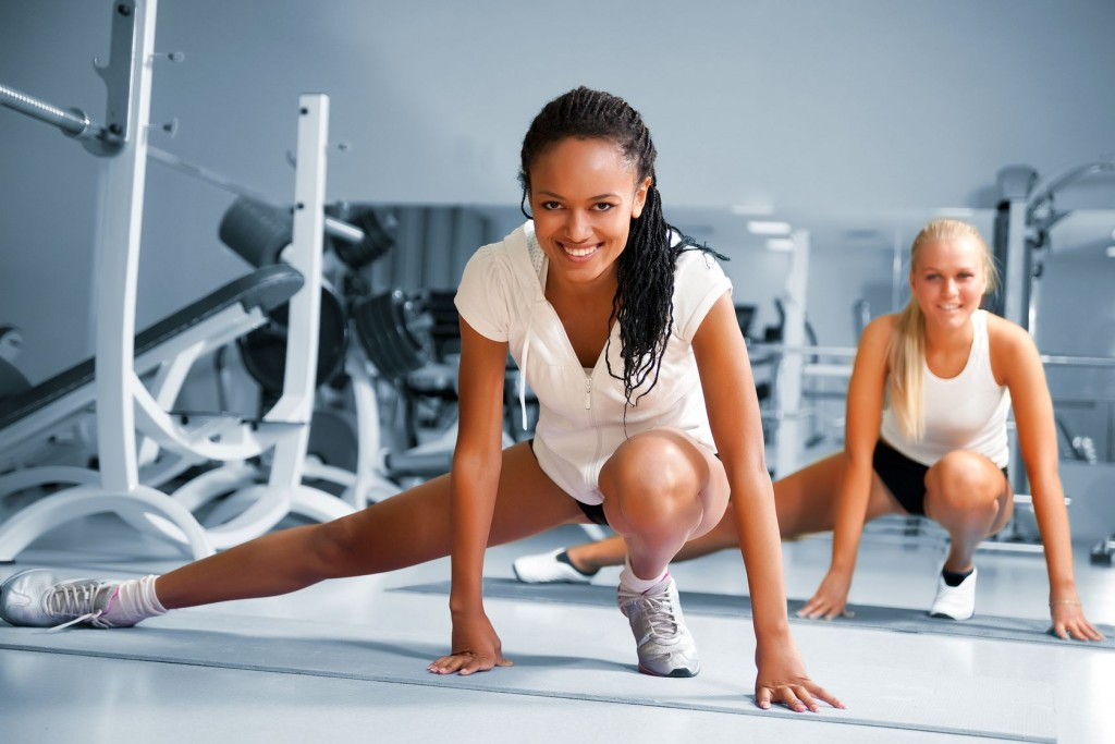 two women at fitness club completing working toward new year fitness goals