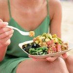 woman eating traditional poke bowl