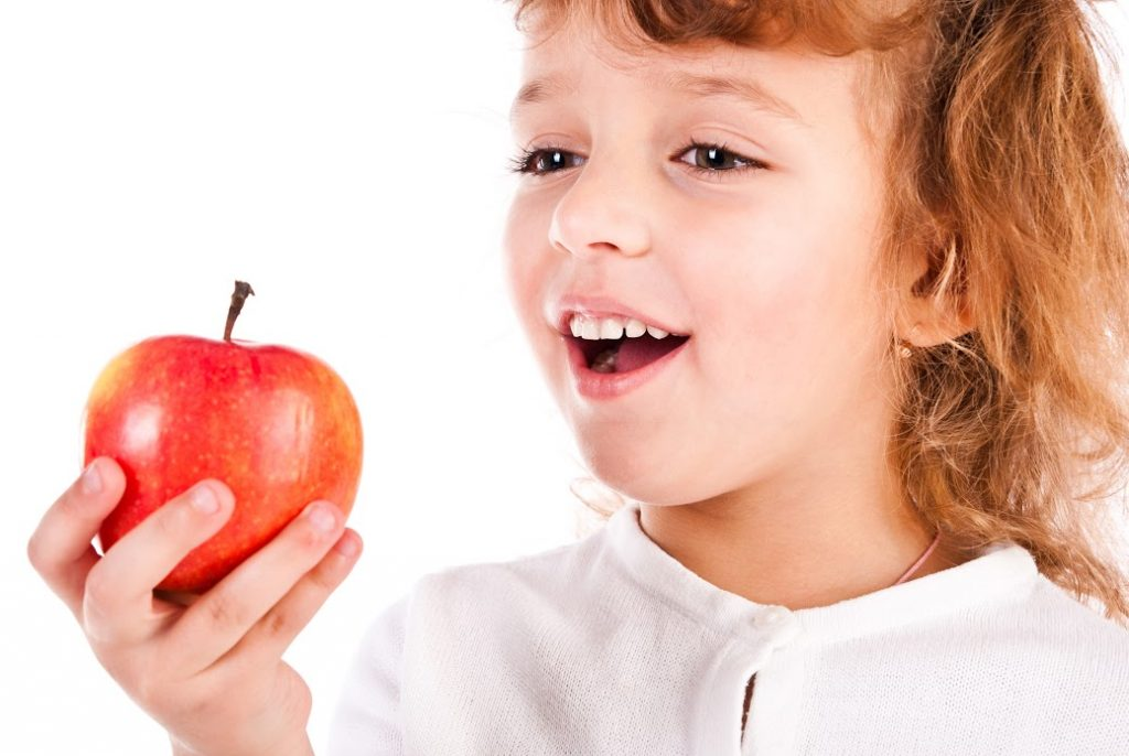 child eating apple against white background
