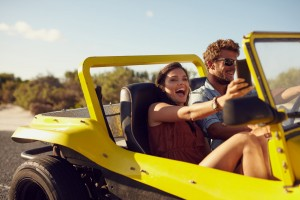 happy couple riding in beach buggy