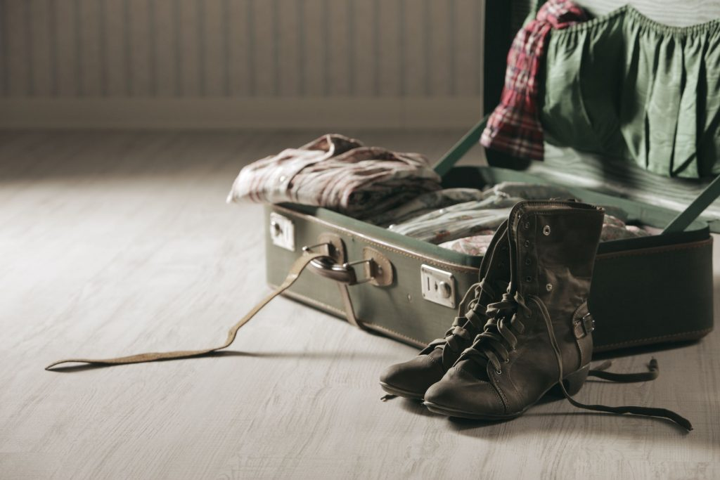 open suitcase with clothes and boots on wooden floor
