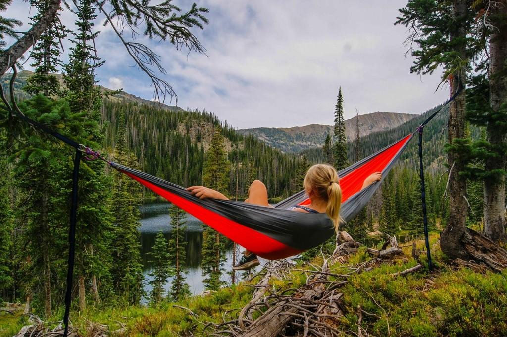 woman relaxing in hammock in forest