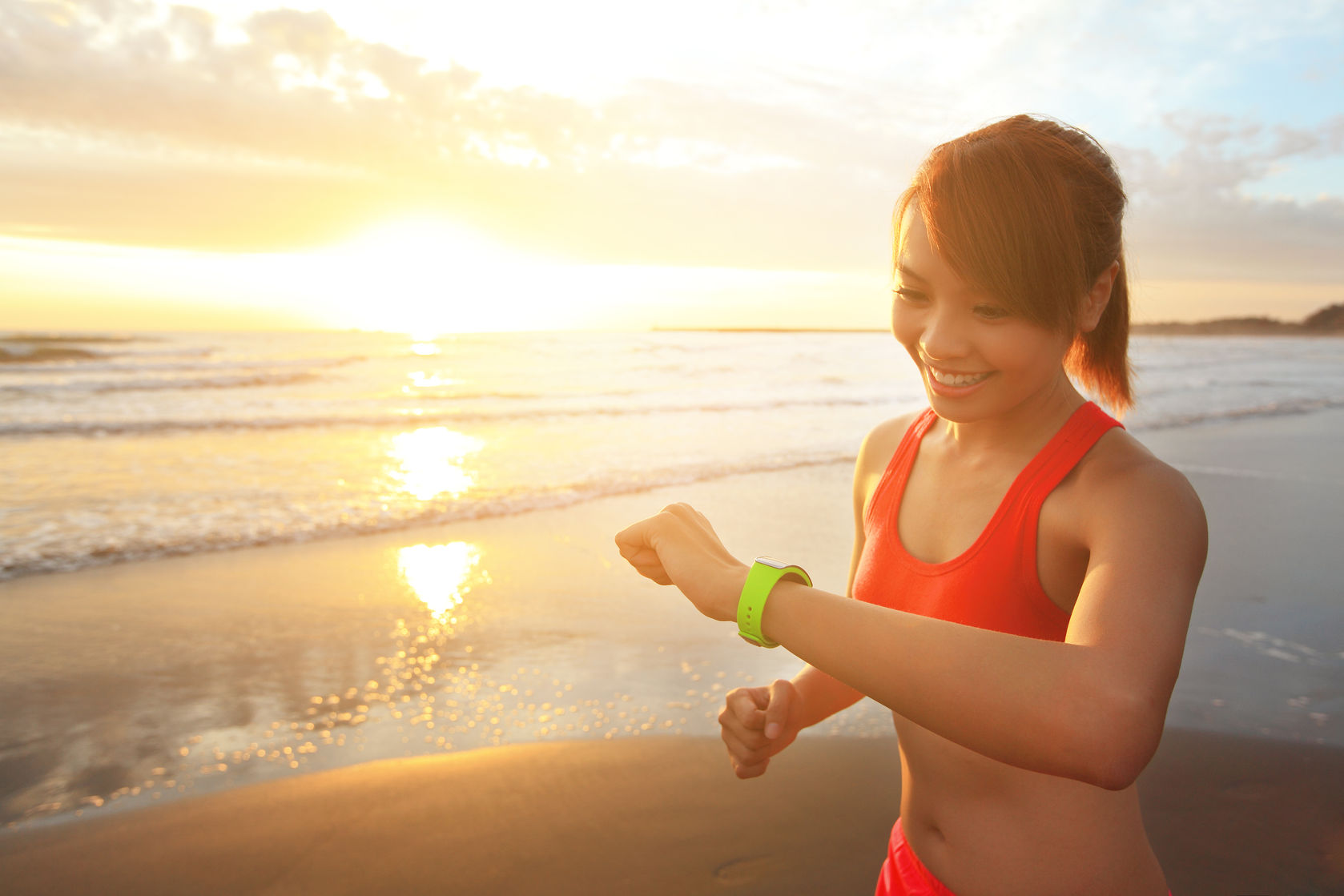 woman with fitness watch exercising on beach shore