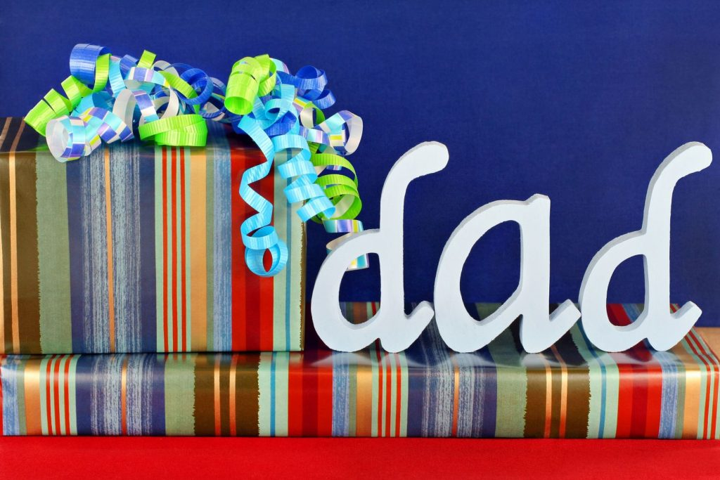 6827579 - masculine wrapped gifts with ribbons and the word dad on top.  ideal for dad's birthday or father's day.
