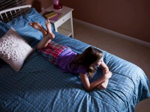 Preteen girl (12 years) lying on bed in pajamas, watching TV.